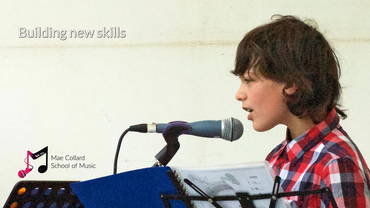 Boy sings into microphone - Building new skills