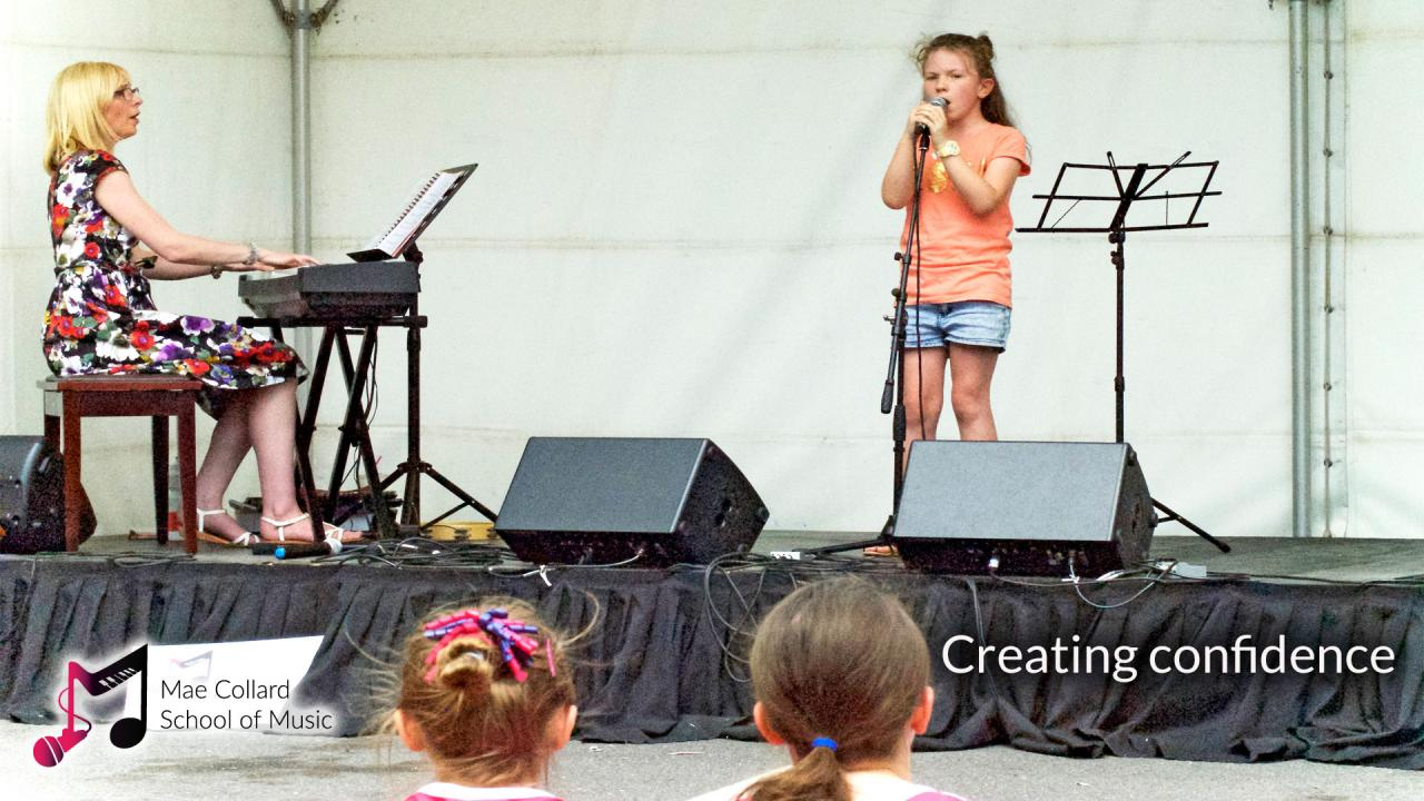 Girl and teacher performing, audience watches - Creating confidence