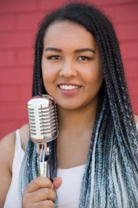 Tahlia Makunde smiling with a microphone